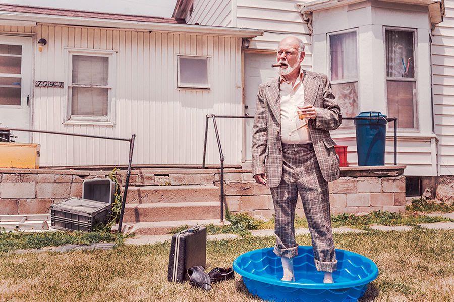 Man having drink in suit in a paddling pool